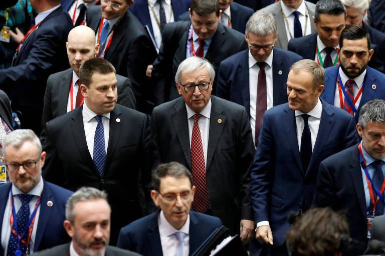 O premiê da Estônia Juri Ratas (esq.), o líder da Comissão Europeia Jean-Claude Juncker e o presidente do Conselho Europeu Donald Tusk chegam para a cúpula em Bruxelas