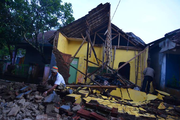 Homem caminha em meio a escombros de uma casa destruída pelo terremoto que atingiu Java, na Indonésia