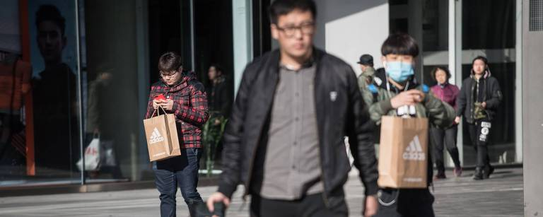 Pessoas passeiam pelo distrito comercial de Sanlitum, em Pequim – Fred Dufour/AFP