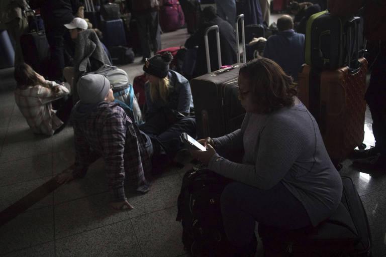 Pessoas aguardam informações no saguão do aeroporto; a prefeitura abriu um abrigo para receber os passageiros afetados que não tinham onde ficar