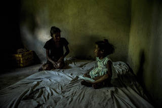 María Carolina Merchán, who weighs 66 pounds, with her daughter Marianyerlis Acosta, 6, whose weight fluctuates between 20 and 29 pounds, depending on how much food she is able to get, in Ocumare Del Tuy, Venezuela.