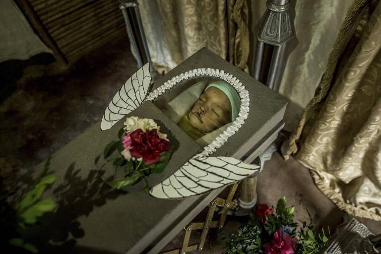 Parentes colocam asas no caixão de Kenyerber Aquino, que morreu aos 17 meses de desnutrição