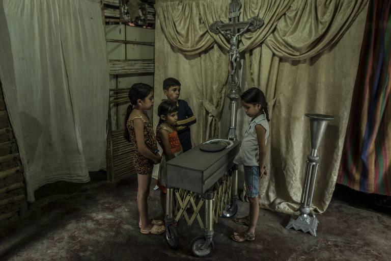 Primos de Kenyerber Aquino olham o caixão com o corpo do menino que morreu de desnutrição