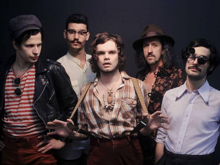 Cinco integrantes da banda posam para foto