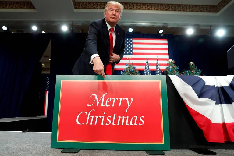 O presidente Donald Trump aponta para placa de 'Feliz Natal' em evento sobre reforma tributária