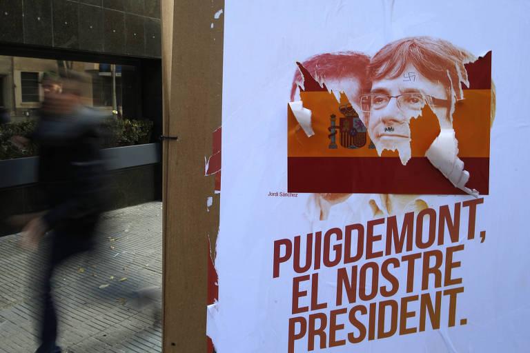 Cartaz do ex-presidente da Catalunha Carles Puigdemont é vandalizado com bandeira espanhola