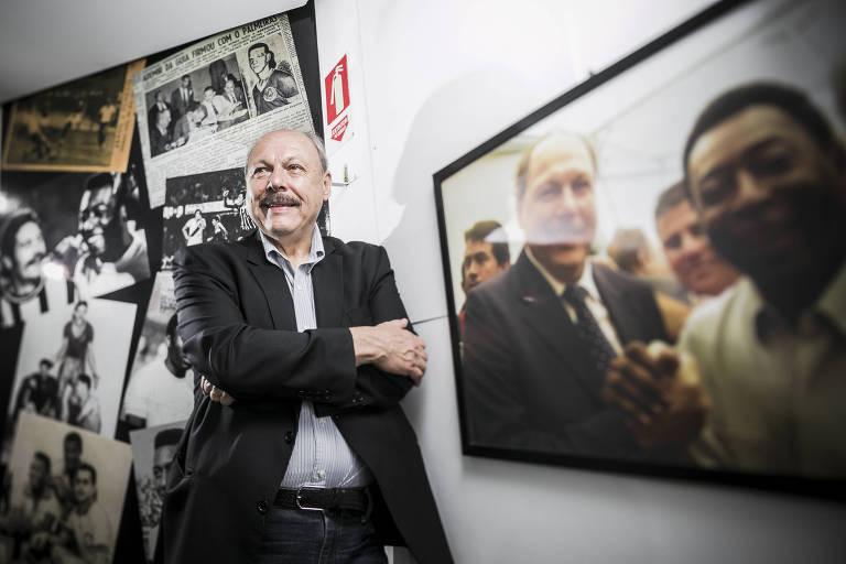 De braços cruzados ao lado de foto com Pelé, José Carlos Peres em entrevista para a Folha após ser eleito presidente do Santos, em dezembro