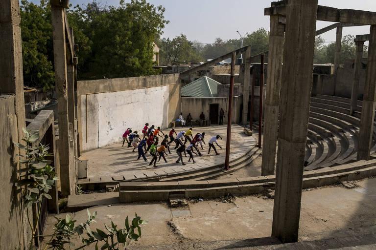 A trupe do Estado de Borno, um grupo artístico de Maiduguri, ensaia apresentação de música e dança em anfiteatro da cidade nigeriana