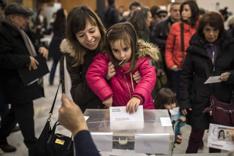 Mulher segura filha que deposita o voto na urna durante a eleição em Barcelona