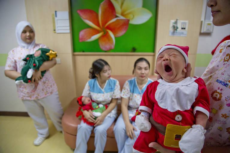 Enfermeiras vestiram recém-nascidos com roupas natalinas no hospital Paolo em Bancoc, na Tailândia