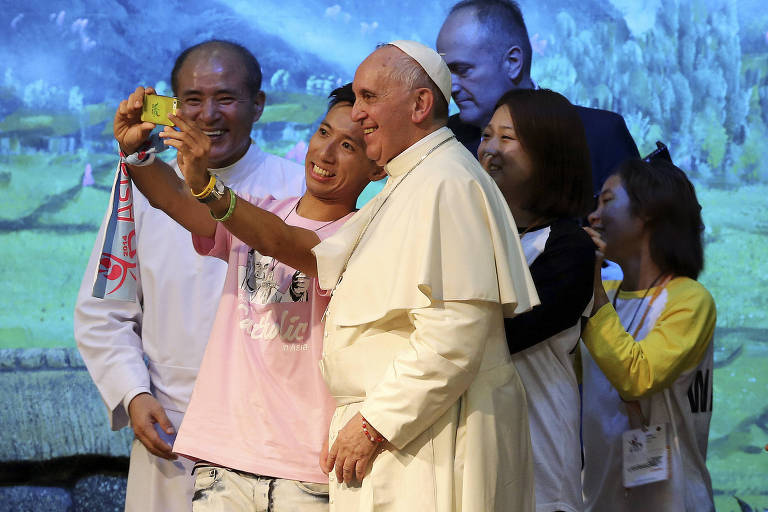 Pope Francis poses for a selfie with young people during a meeting with Asian youth at the Solmoe Sanctuary in Dangjin, South Korea, Friday, Aug. 15, 2014. Pope Francis urged Catholic youth on Friday to renounce the materialism that afflicts much of Asian society today and reject