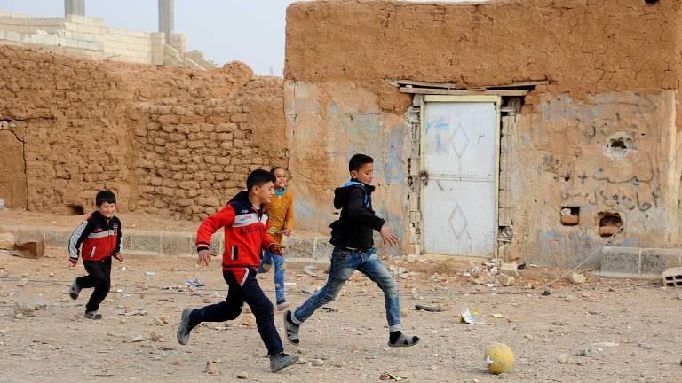 Crianças jogam bola na rua em periferia de Raqqa, na Síria; cidade era um dos bastiões da facção Estado Islâmico, expulsa pelas forças rebeldes em outubro
