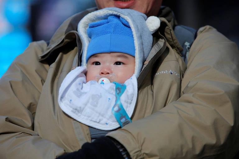 Bebê agasalhado para o frio na Times Square, em Nova York