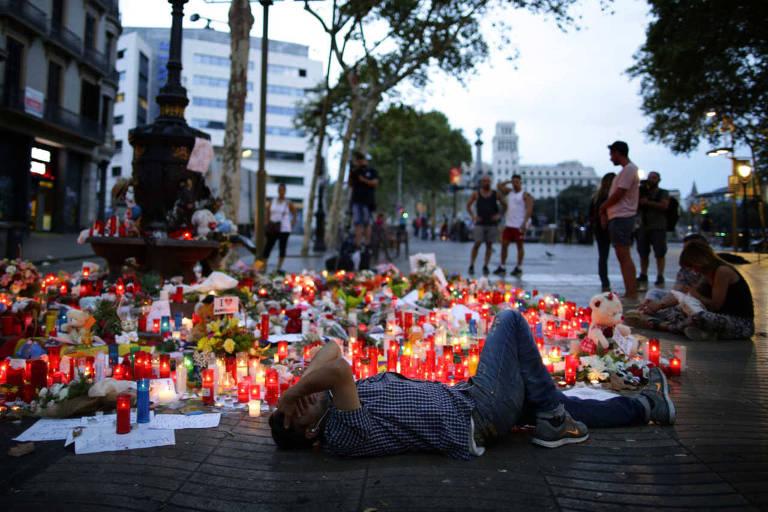 Homem deita e chora ao lado de memorial às vítimas do atentado de 17 de agosto em Barcelona