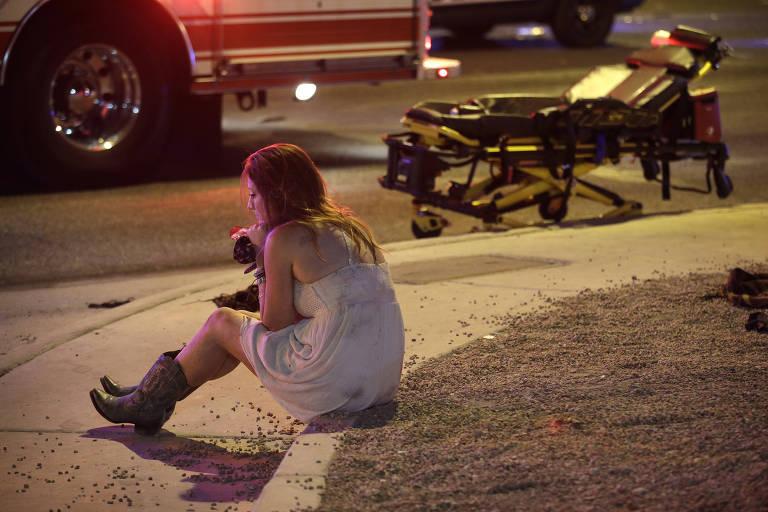Mulher em choque senta ao lado do local que foi atingido pelo ataque a tiros de Las Vegas, em outubro