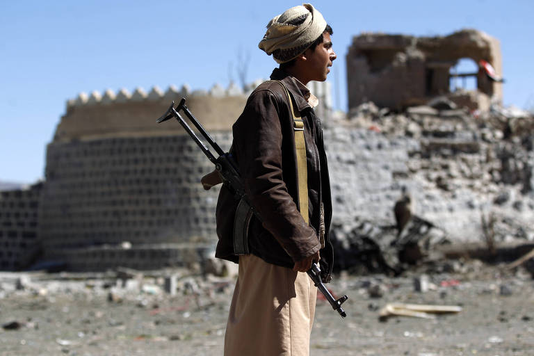 Armado com fuzil, jovem observa destruição provocada por ataque saudita em Sanaa, no Iêmen