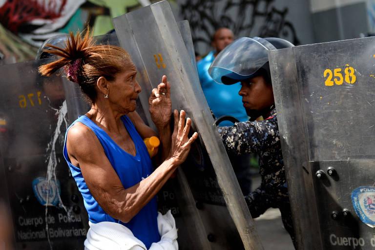 Mulher confronta guarda nacional em manifestação contra escassez de comida em Caracas