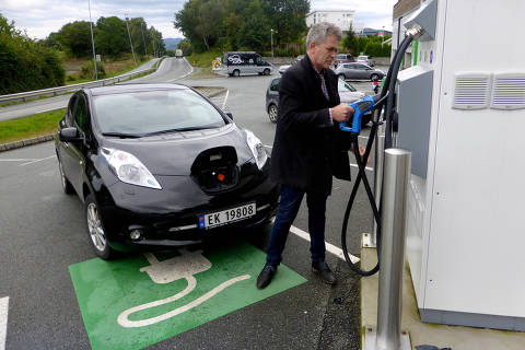 FILE PHOTO: A man recharges his Nissan Leaf electric car in Finnoey, Norway September 8, 2017. REUTERS/Alister Doyle/File Photo ORG XMIT: SJF301