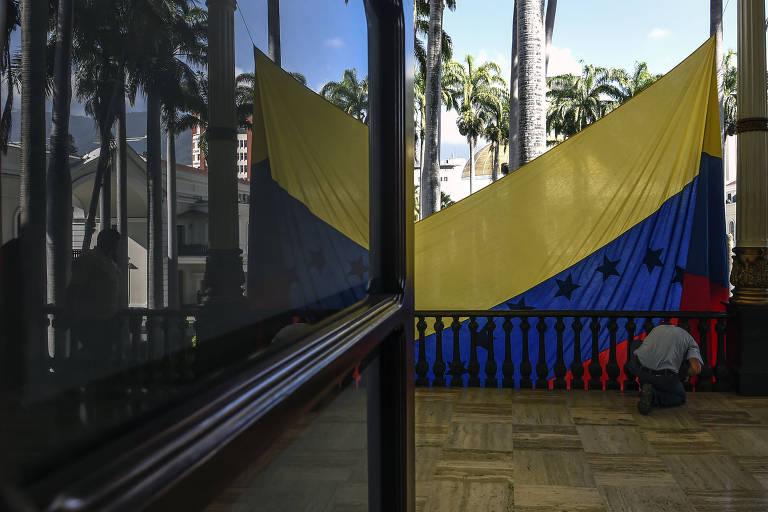 Homem é visto em uma varanda levantando a bandeira venezuelana, que aparece pela metade. A foto é tirada de dentro do prédio.