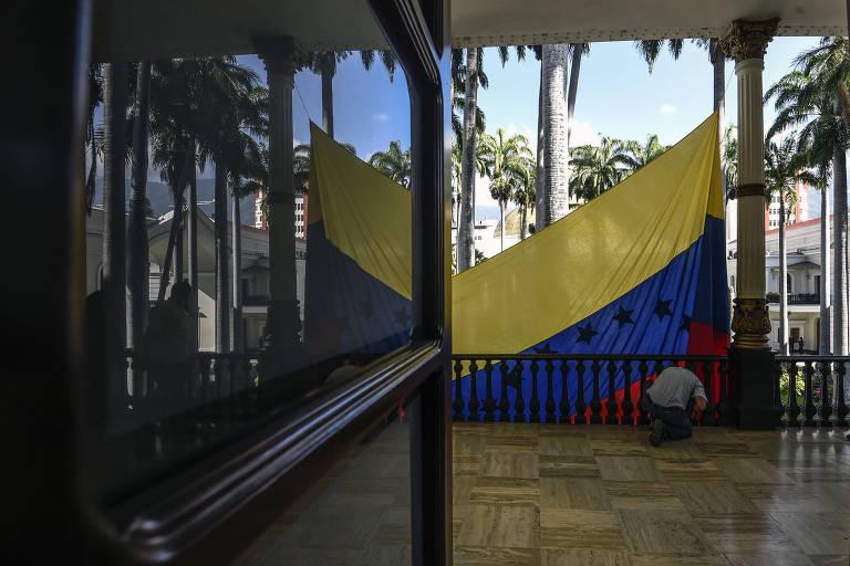 Funcionário hasteia bandeira na Assembleia Nacional da Venezuela, de maioria opositora