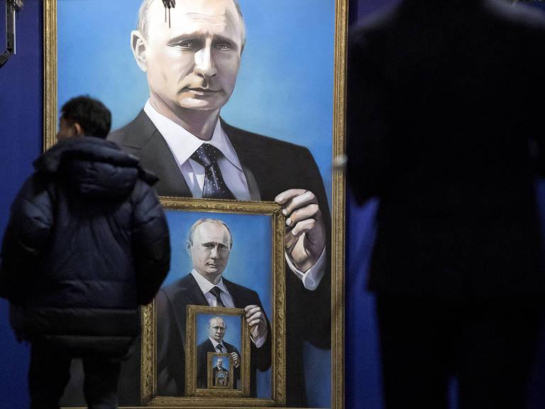 Visitantes observam quadros com retratos de Putin em exposição em museu de Moscou