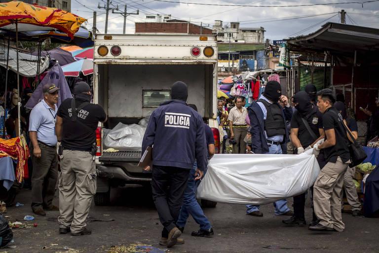 Policiais carregam um corpo em San Salvador, capital de El Salvador, país que sofre com a violência