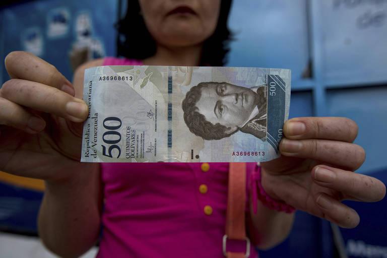 Mulher segura nota de 500 bolívares; oposição calcula inflação de 2.616% na Venezuela