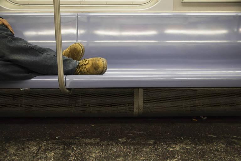Pés de homem sem-teto que dorme em trem da linha E do metrô de Nova York devido a frio intenso