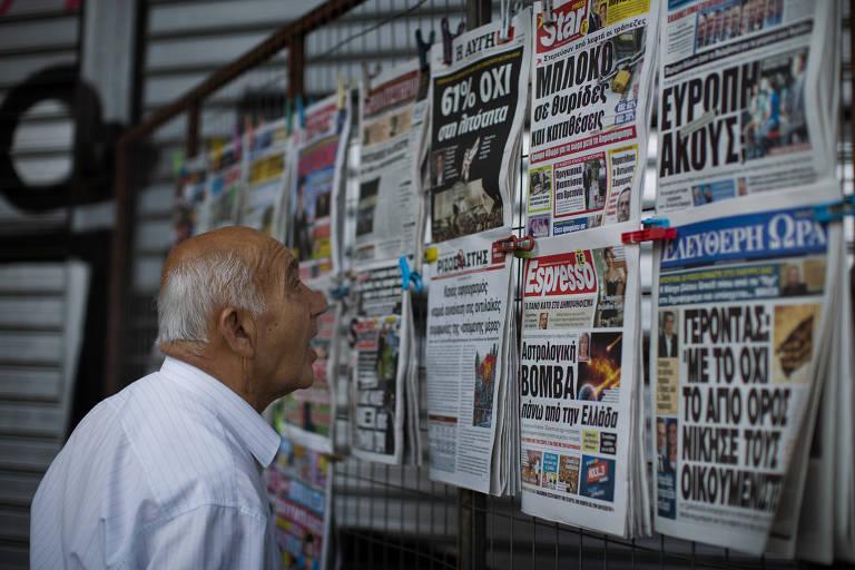 Homem vê jornais expostos em banca de Atenas, na Grécia