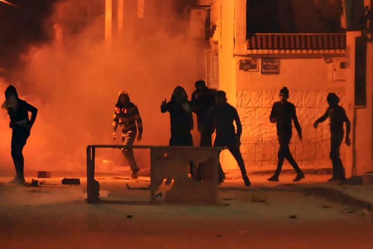 Manifestantes atiram pedras e pedaços de pau em meio ao gás lacrimogêneo em protesto em Tebourba