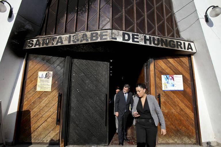 O vice-ministro do Interior do Chile, Aleuy Mahmud (centro), deixa a igreja Santa Isabel de Hungria, atacada em Santiago (Chile)
