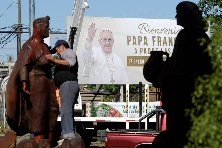 Homem limpa escultura de mapuche diante de cartaz com o papa Francisco em Temuco, no Chile