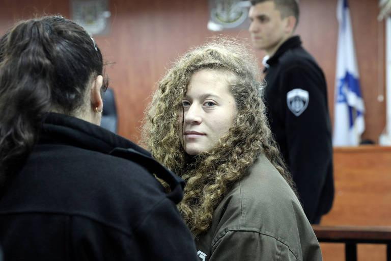 Ahed Tamimi ao lado de guardas israelenses em um tribunal militar próximo à Cisjordânia
