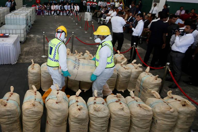 Policiais carregam saco de cocaína apreendida que será destruída, em Katunayake, no Sri Lanka