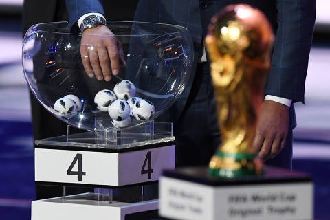 A draw assistant picks up a ball next to the official FIFA World Cup trophy during the 2018 FIFA World Cup football tournament final draw at the State Kremlin Palace in Moscow on December 1, 2017.