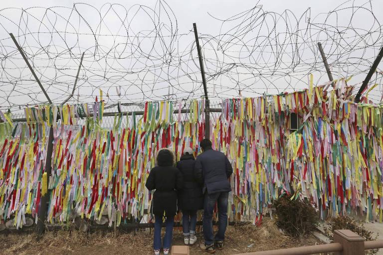 Famílias pela cerca onde são colocadas fitas de desejo de unificação das Coreias em Paju