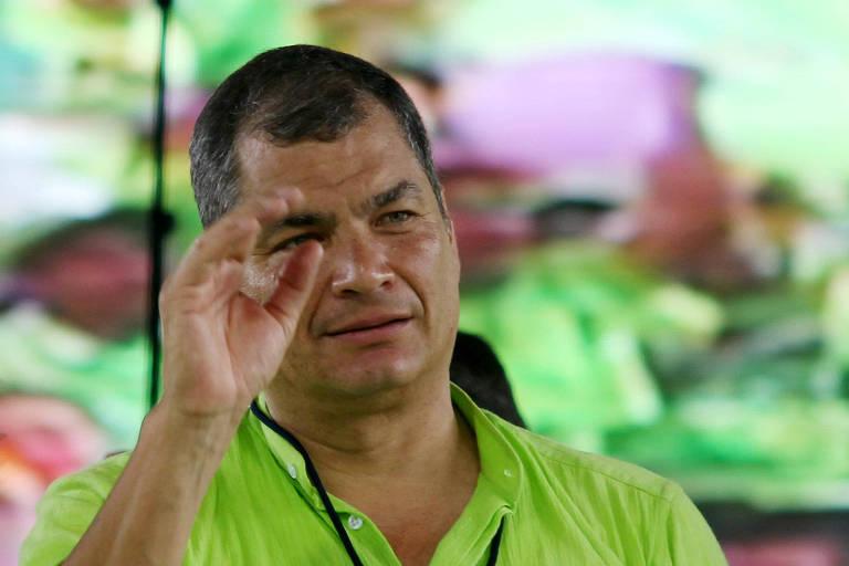 De camisa verde, Correa faz gesto com a mão esquerda enquanto fala em comício. Ele aparece do peito para cima.