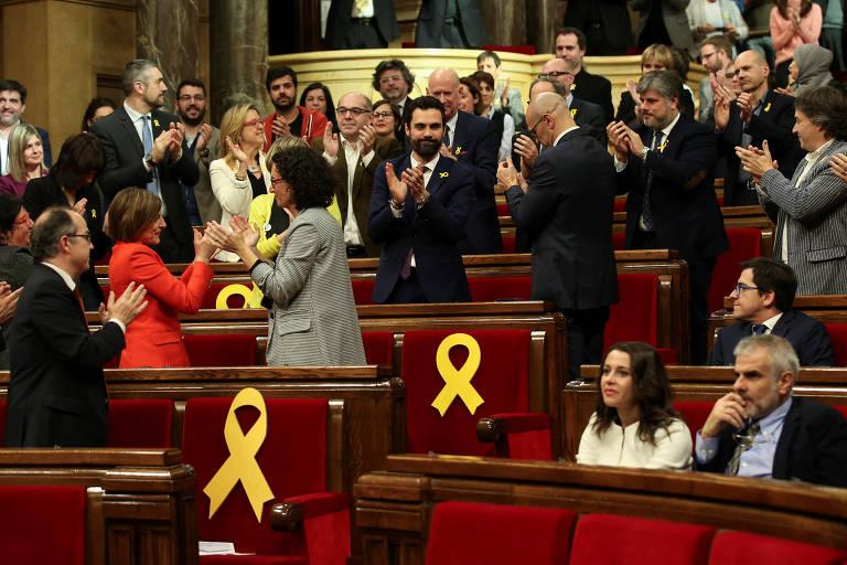 Deputados aplaudem após Roger Torrent (no centro, de azul) ser eleito o presidente do novo Parlamento catalão; assentos com fitas amarelas simbolizam os parlamentares detidos ou foragidos