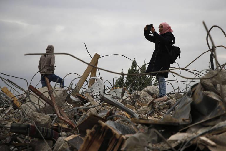 Palestinos andam nos escombros de casa em Jenim, na Cisjordânia, que foi demolida pela polícia