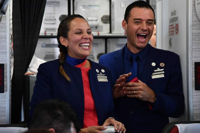 Os tripulantes Paula Podest (esq) e Carlos Ciufffardi sorriem após serem casados pelo papa Francisco em voo entre Santiago e Iquique, no Chile