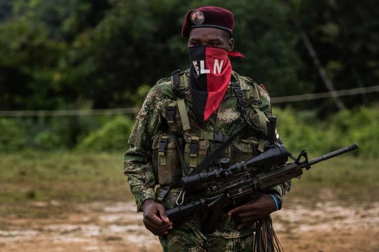 Com fuzil na mão, roupa camuflada e queixo coberto por uma bandeira do ELN, guerrilheiro participa de treinamento do grupo no departamento de Chocó, na Colômbia