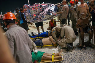 Paramedics help the injured after a vehicle ran over some people at Copacabana beach in Rio de Janeiro, Brazil