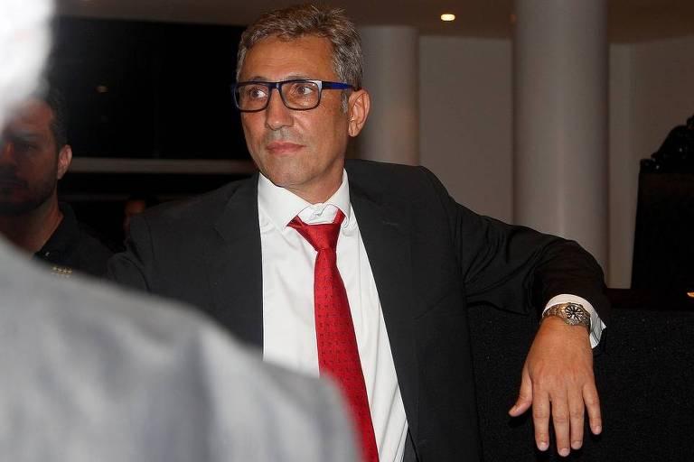 Novo presidente do vasco com terno e gravata vermelha, olhando para o lado