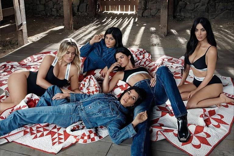 """Kim Kardashian, Kendall Jenner, Khloé Kardashian e Kourtney Kardashian aparecem sensuais exibindo a barriga, com a exceção de Kylie Jenner, que se """"esconde"""" em um edredom."""