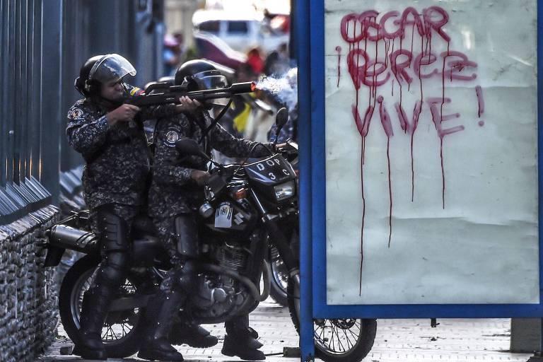 Membro da polícia nacional dispara bala de borracha contra manifestante em Caracas, na Venezuela