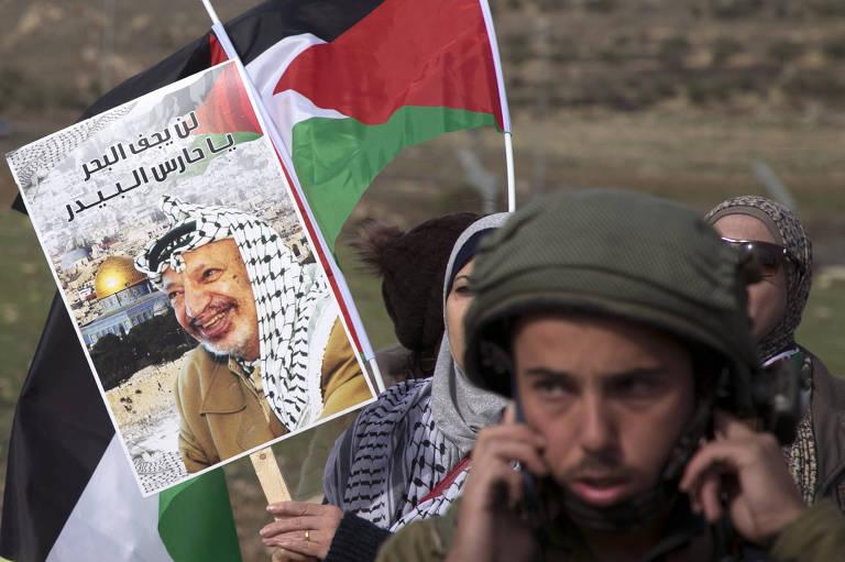 Palestina carrega cartaz de Iasser Arafar e soldado israelense se comunica em protesto em Nablus