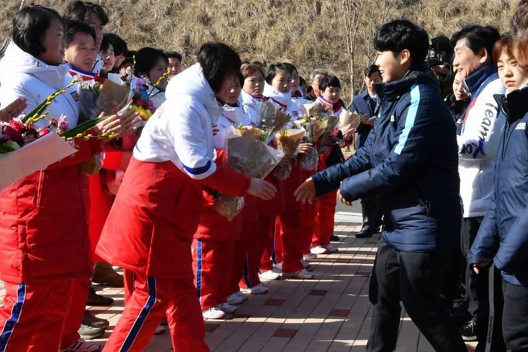 Atletas da Coreia do Norte (esq.) cumprimentam suas colegas do Sul após cruzarem a fronteira