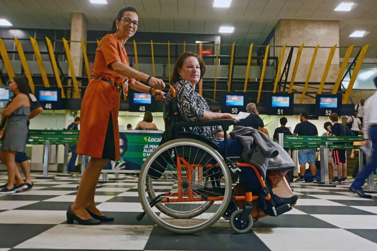 Ana Helena Guerreiro Sonoda, selecionada pela Gol em programa para profissionais maduros, empurra passageira em cadeira de rodas em Congonhas