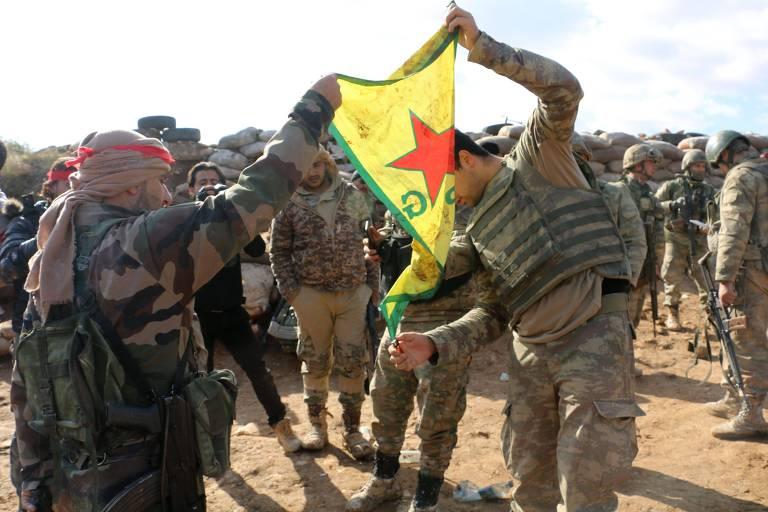 Soldados ligados a Turquia queimam uma bandeira curda na colina de Bursayah