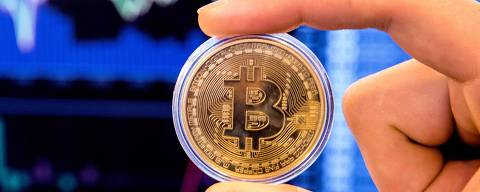 An Israeli holds a visual representation of the digital cryptocurrency Bitcoin, at the